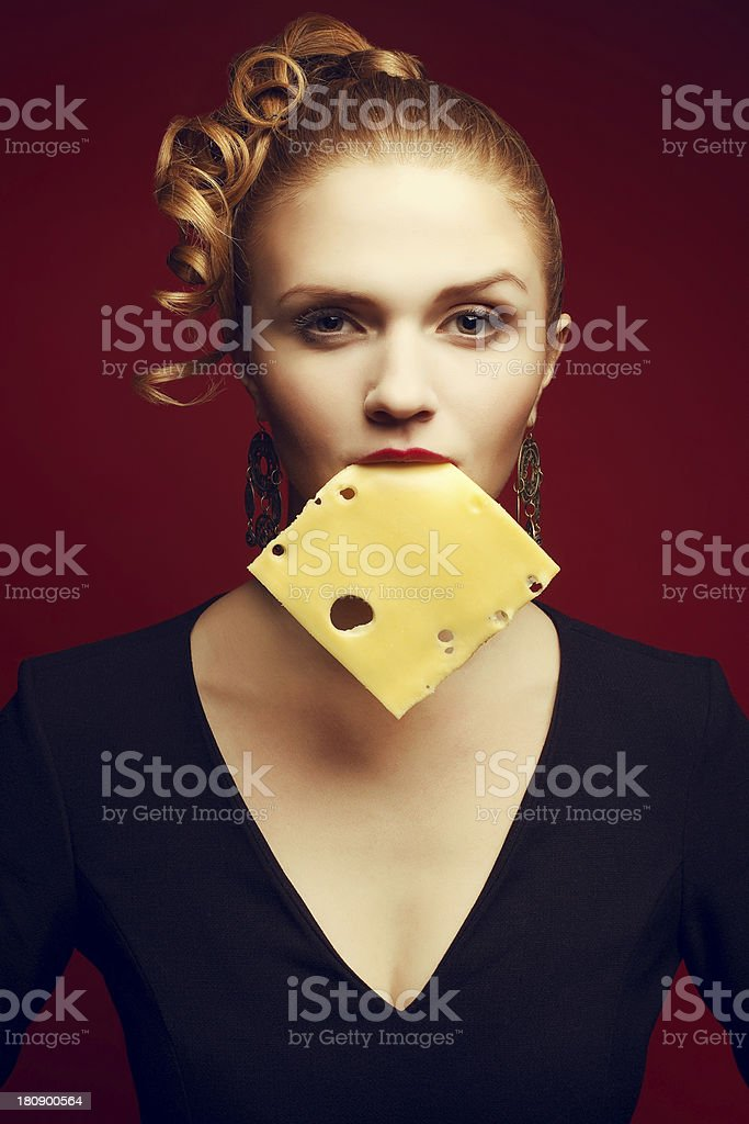Portrait of young woman holding cheese slice in her mouth stock photo