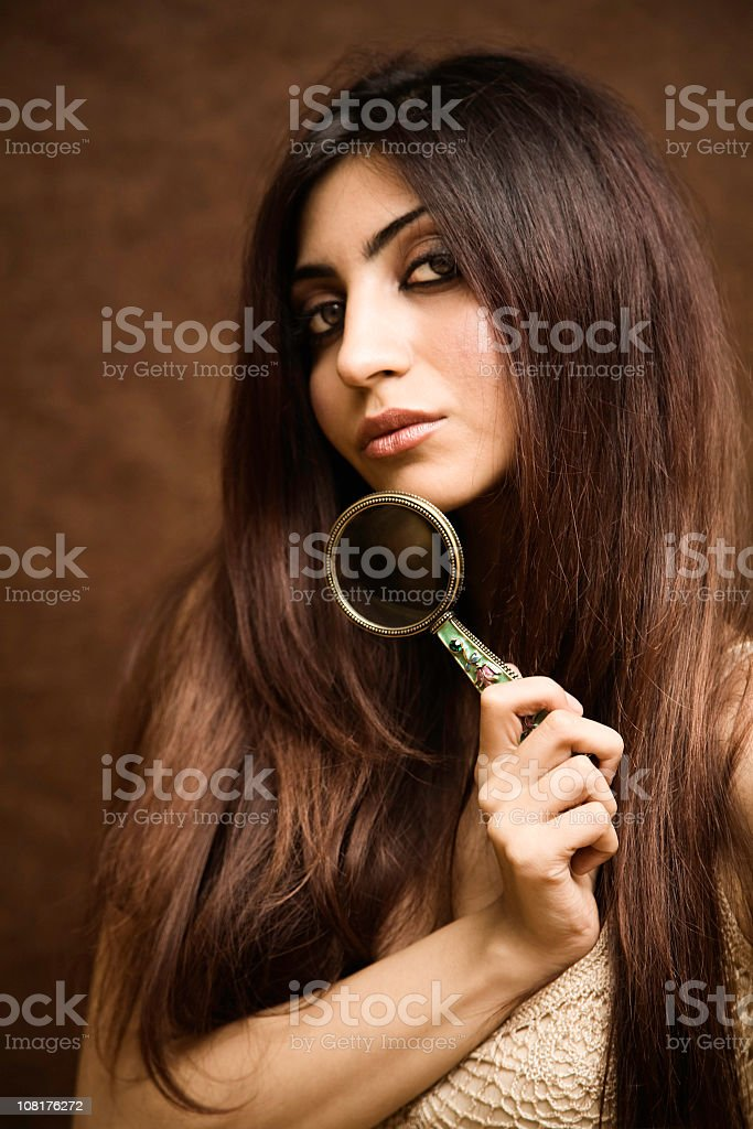 Portrait of Young Woman Holding Magnifying Glass royalty-free stock photo