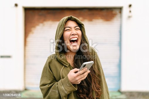 A portrait of a young and happy woman wearing a hoodie and holding a smart phone while laughing.