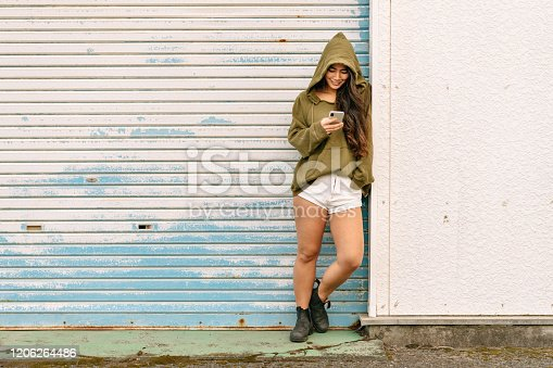 A portrait of a young and happy woman wearing a hoodie and holding a smart phone.
