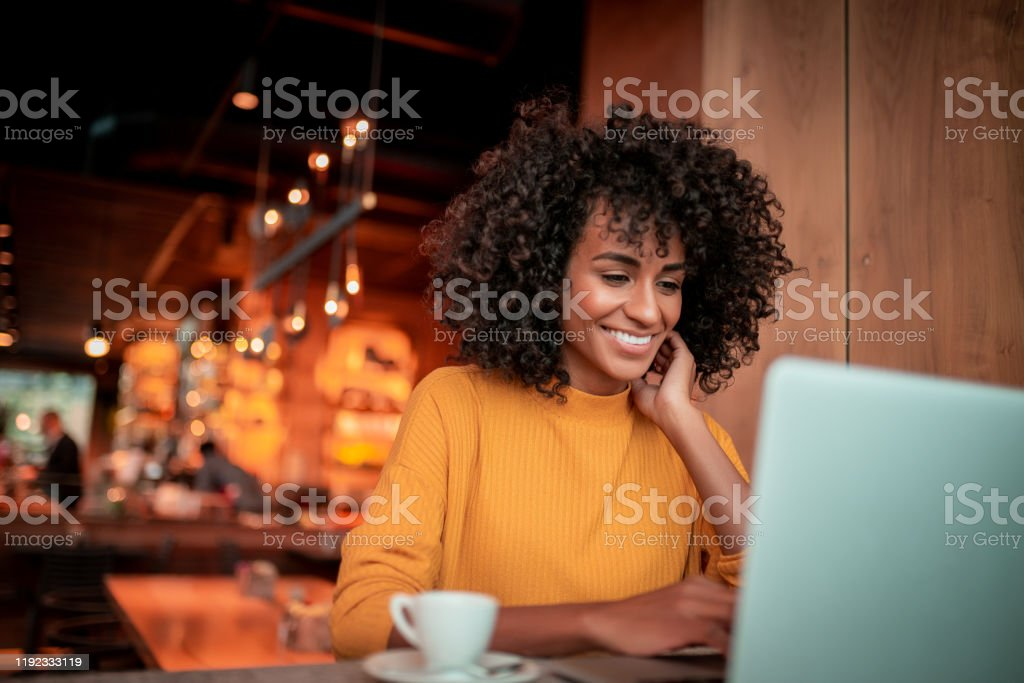 Portrait of young woman in a coffee shop Young beautiful woman sitting in the coffee shop and using a laptop 30-34 Years Stock Photo