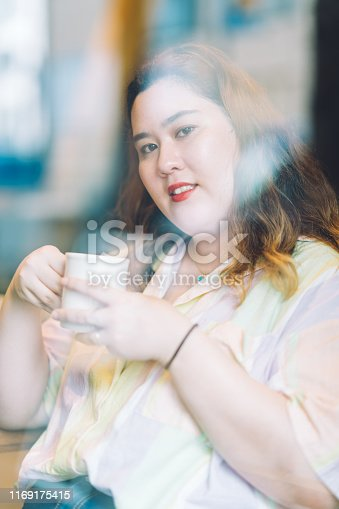 A close-up portrait of young body positive female illustrator in a cafe. A photo is shot outside through a window glass with reflections on it.