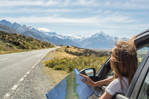 Portrait of young woman in car looking at map