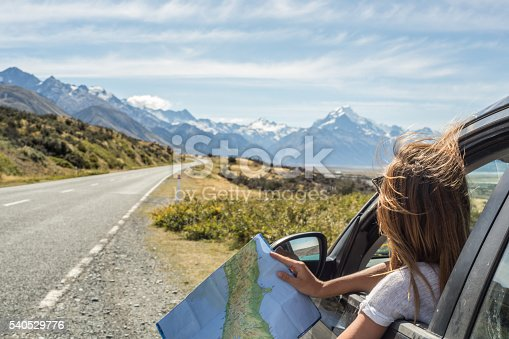 Portrait of a young woman in a car looking at a map for directions.