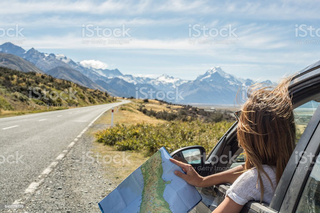 Portrait of young woman in car looking at map stock photo