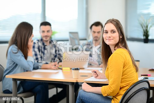 istock portrait of young woman in casual wear working in a creative business startup company office with coworker people in background 653116624