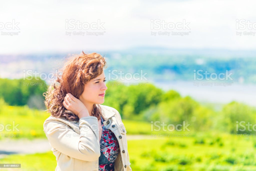 Portrait of young woman in countryside summer during windy day touching hair with river, trees, forest, and hills or mountains in background stock photo