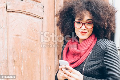 518885222istockphoto Portrait of young woman in front of a wooden door 518282836