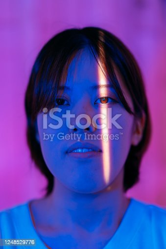 1071416330 istock photo Portrait of young woman in front of neon colored wall while only her eyes lit by sunlight 1248529776