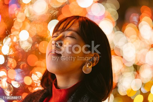 A portrait of a young and beautiful woman in front of orange and red lights.