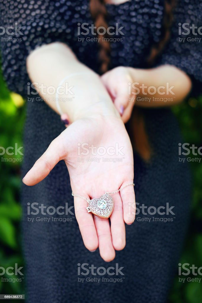 Portrait of young woman in glasses, black chiffon dress with white dots and long braids looking at silver locket gift remembering her lover. stock photo