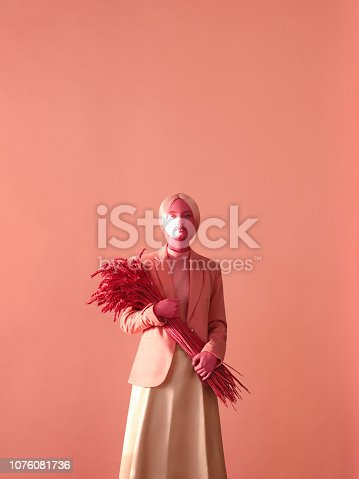 Woman with pink skin make-up and holding bunch of pink ears