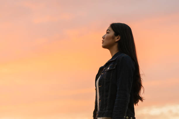 Portrait of young woman in nature during sunset stock photo
