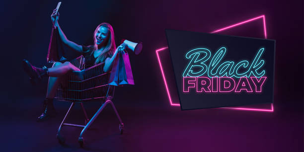 Portrait of young woman in neon light on dark backgound. The human emotions, black friday, cyber monday, purchases, sales, finance concept. Neoned lettering. Selfie, megaphone. Portrait of young woman in neon on dark studio backgound. Human emotions, black friday, cyber monday, purchases, sales, finance concept. Copyspace. Seamless post for instagram. black friday sale neon stock pictures, royalty-free photos & images