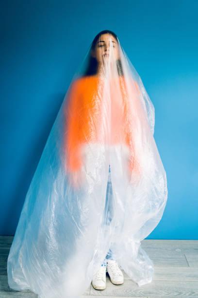porträt der jungen frau in orange vor der blauen wand mit nylon-plastikbeutel bedeckt, antiverschmutzungsverschmutzung retten den planeten ozeane ökologie konzept - windbeutel stock-fotos und bilder