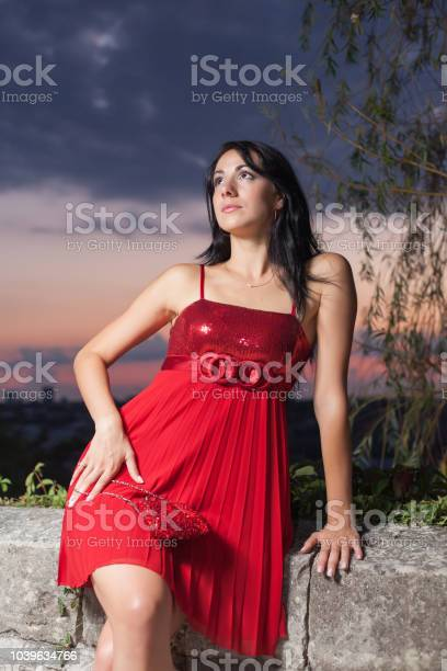 Photo of Portrait of young woman in red sleeveless dress
