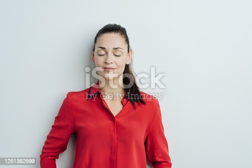 Young brunette woman in red blouse standing with her eyes shut against white wall background. Half-length front portrait
