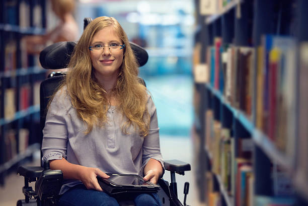 portrait of young woman in wheelchair in library - wheelchair stock photos and pictures