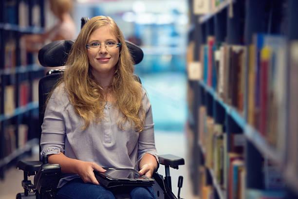 ritratto di giovane donna in sedia a rotelle in biblioteca - sedia a rotelle foto e immagini stock