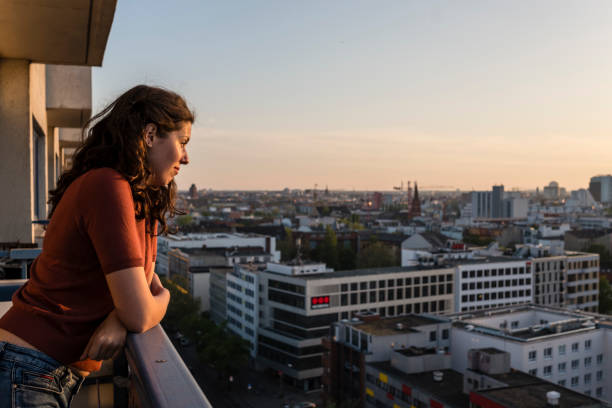portrait of young woman leans at balcony and looks over Berlin skyline while sunset stock photo