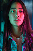 A close-up portrait of a young woman lit by colorful neon lights at night.