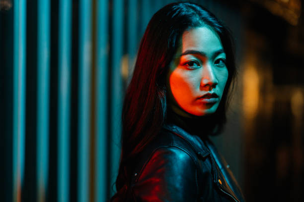 Portrait of young woman lit by neon colored light in city at night stock photo