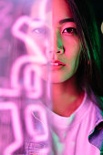istock Portrait of young woman lit by pink neon light 1192304374