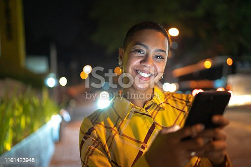 istock Portrait of young woman looking at camera and using phone 1161423948