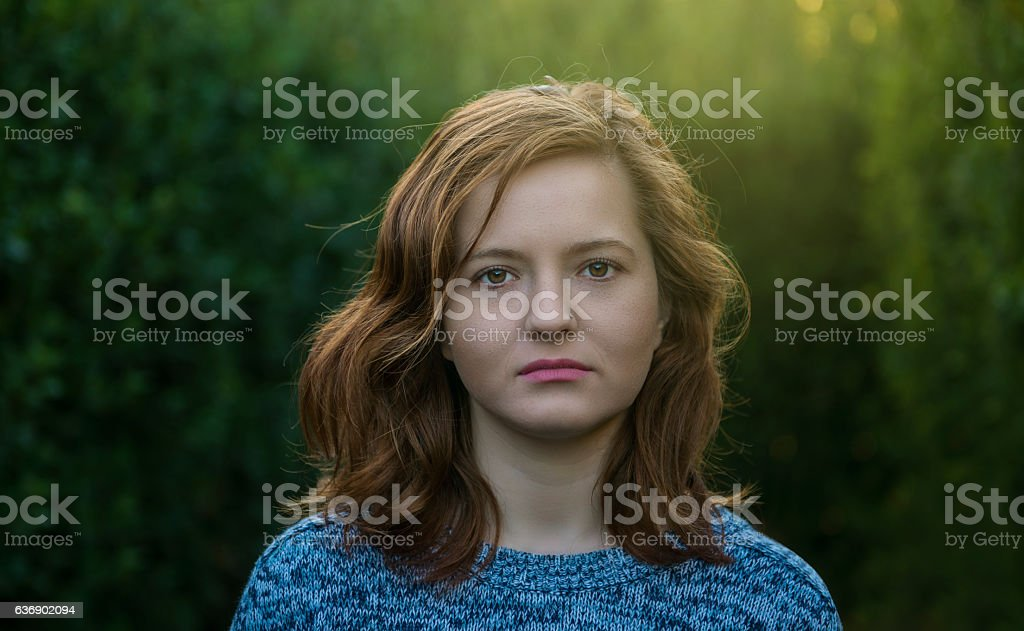Portrait of young woman looking at camera with blank expression stock photo