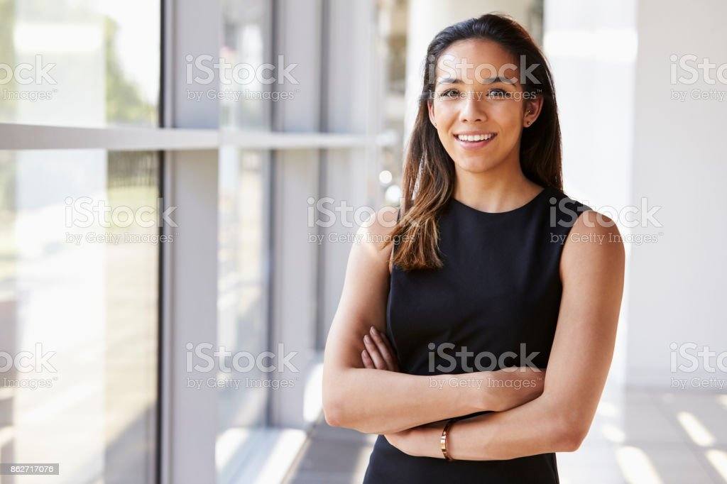 Portrait of young woman looking to camera with arms crossed stock photo