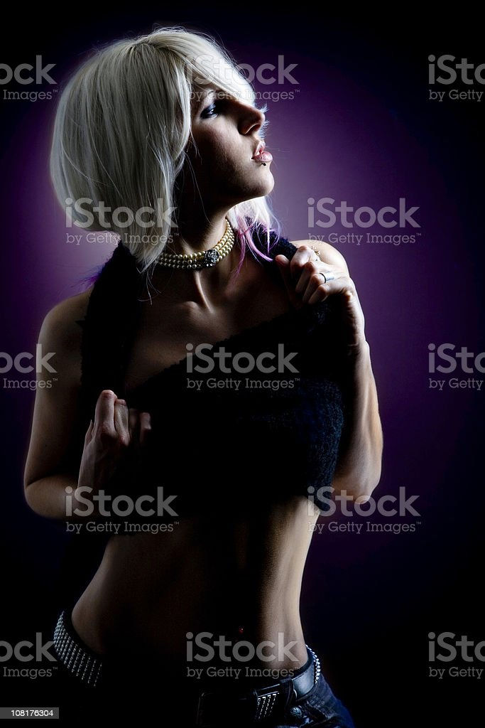 Portrait of Young Woman, Low Key on Purple Background stock photo