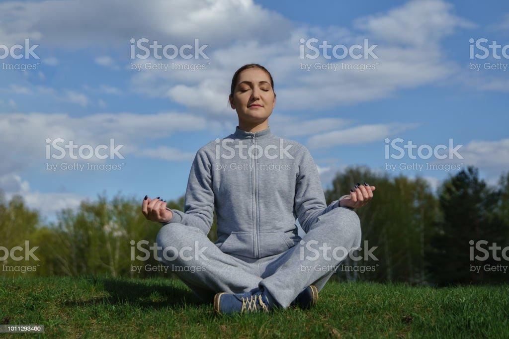 Porträt der jungen Frau in Pose des Lotus auf dem grünen Rasen im Freien zu meditieren – Foto