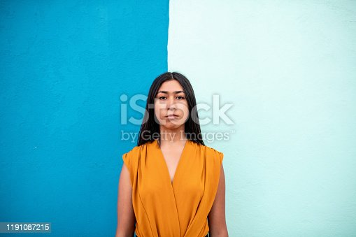 Portrait of a young woman against two colored wall