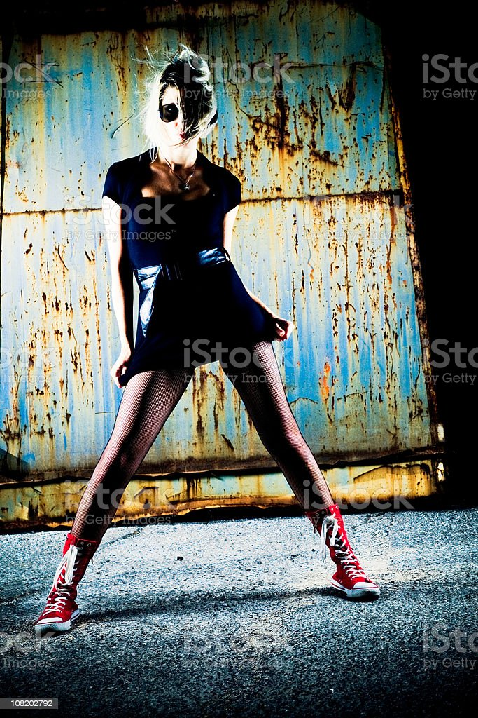 Portrait of Young Woman Posing Near Rusted Metal Containers royalty-free stock photo