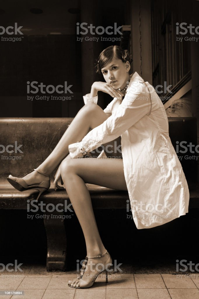 Portrait of Young Woman Posing on Bench, Sepia Toned royalty-free stock photo