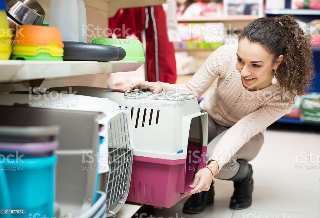 Portrait of young woman purchasing pet kennels stock photo