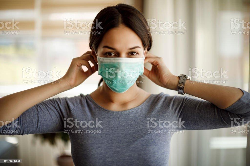 Portret van jonge vrouw die op een beschermend masker voor coronavirusisolatie zet - Royalty-free Aanbrengen Stockfoto