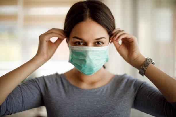 Portrait of young woman putting on a protective mask Portrait of young woman putting on a protective mask covid mask stock pictures, royalty-free photos & images