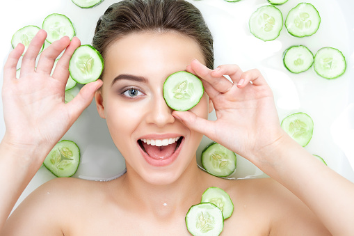 Portrait of sexy beauty Caucasian female woman with clean pure skin taking spa relaxing in bath with cucumber slices white soap shampoo water. Skin beauty health care concept. Body part bare shoulder