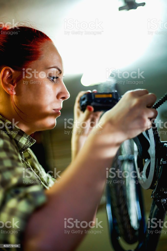 Portrait of young woman repairing bicycle wheel stock photo