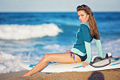 Portrait of young woman resting and enjoying the ocean after windsurfing