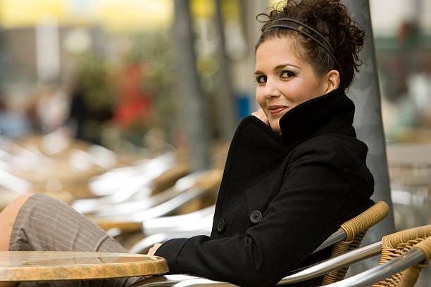 portrait of young woman sitting down and wearing peacoat - double_p stockfoto's en -beelden
