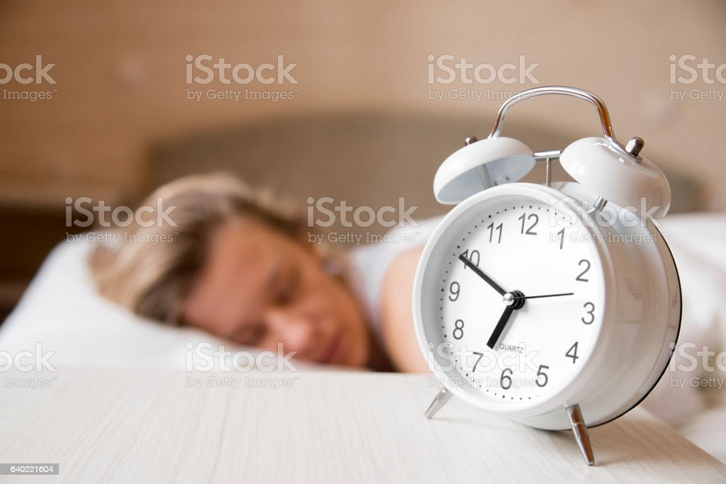 Portrait Of Young Woman Sleeping With Alarm On Side stock photo