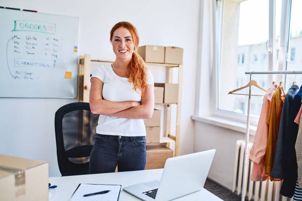 Portrait of young woman smiling at camera with crossed arms while standing in office of her new online business stock photo