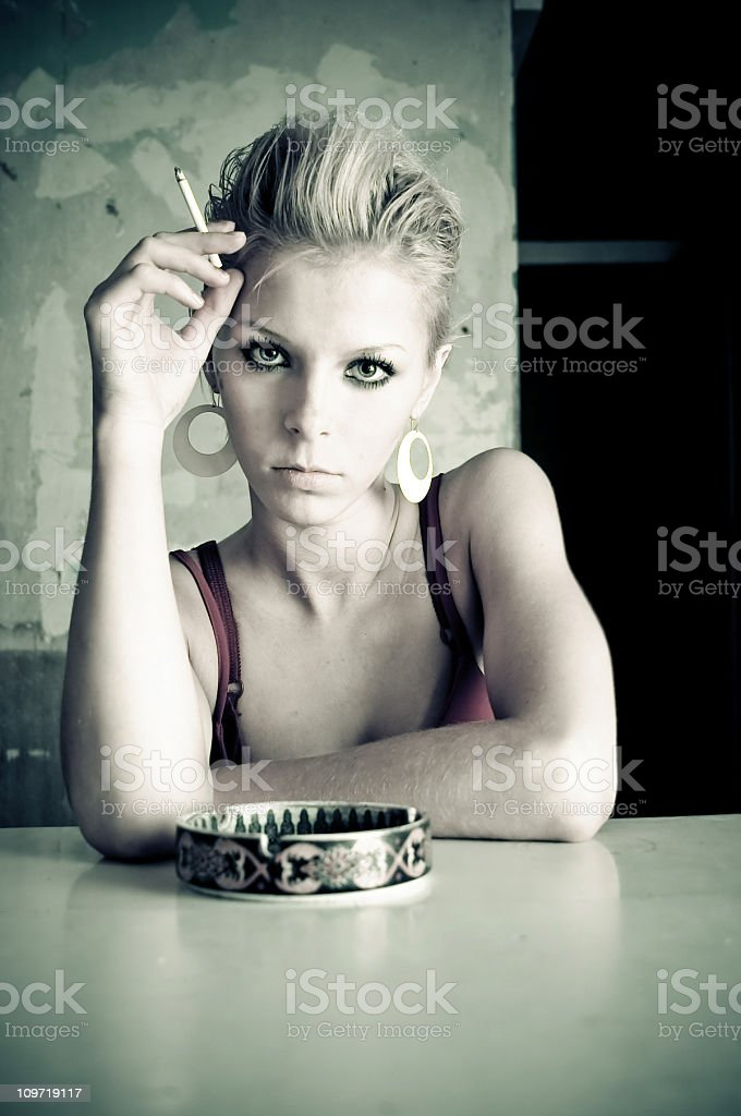 Portrait of Young Woman Smoking Cigarette at Table with Ashtray royalty-free stock photo