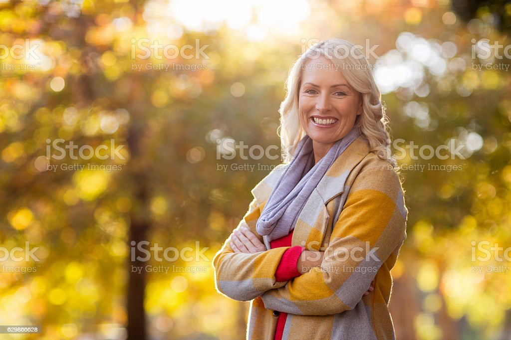 Portrait of young woman standing at park stock photo
