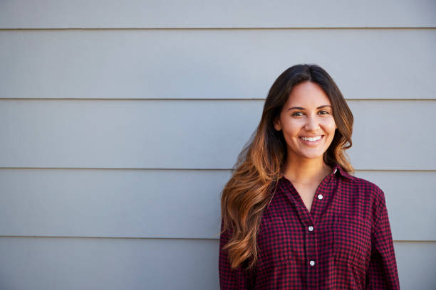 Portrait Of Young Woman Standing Outside Grey Clapboard House stock photo