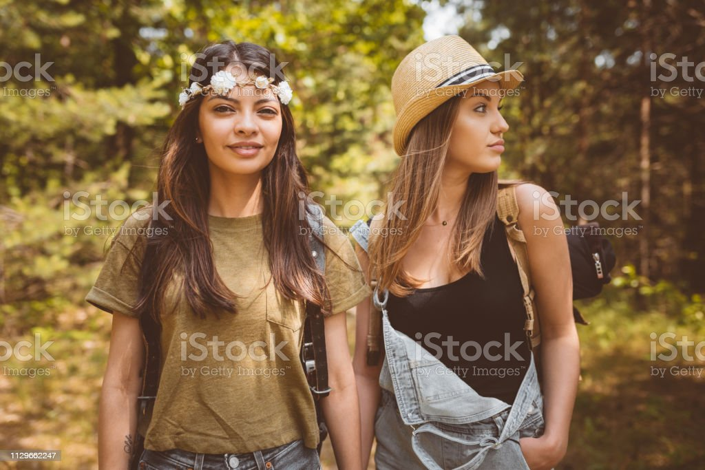 Portrait of young woman standing with friend Portrait of beautiful young woman standing with friend. Female hipsters are exploring forest. They are spending weekend together. 20-24 Years Stock Photo