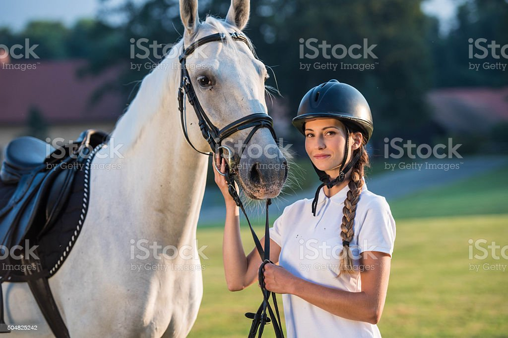 Portrait of young woman standing with horse stock photo