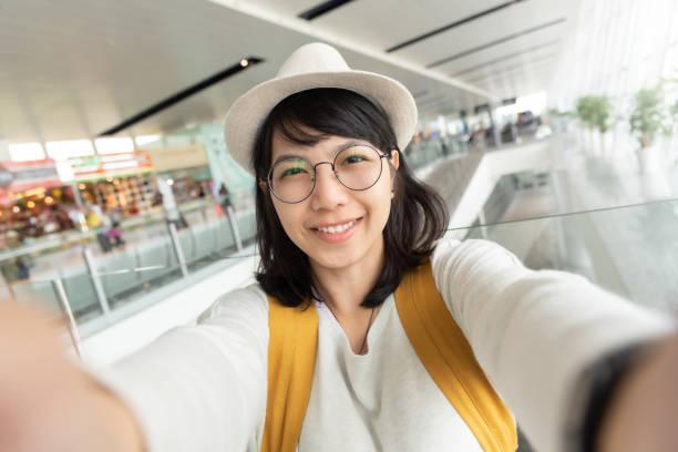 Retrato de joven viajera usar gafas y sombrero tomando selfie. - foto de stock
